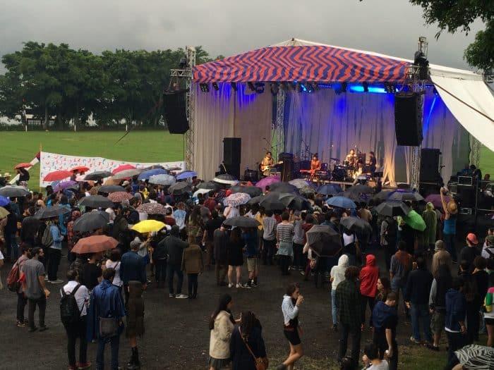 An umbrella audience enjoying Buscabulla's performance. Elizabeth Lang/ The Tico Times