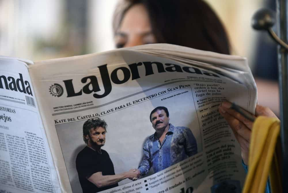 "A woman reads La Jornada newspaper in Mexico City, on Jan. 10, 2016, showing a photo of drug lord Joaquín Guzmán, aka ""El Chapo,"" right, shaking hands with actor Sean Penn."