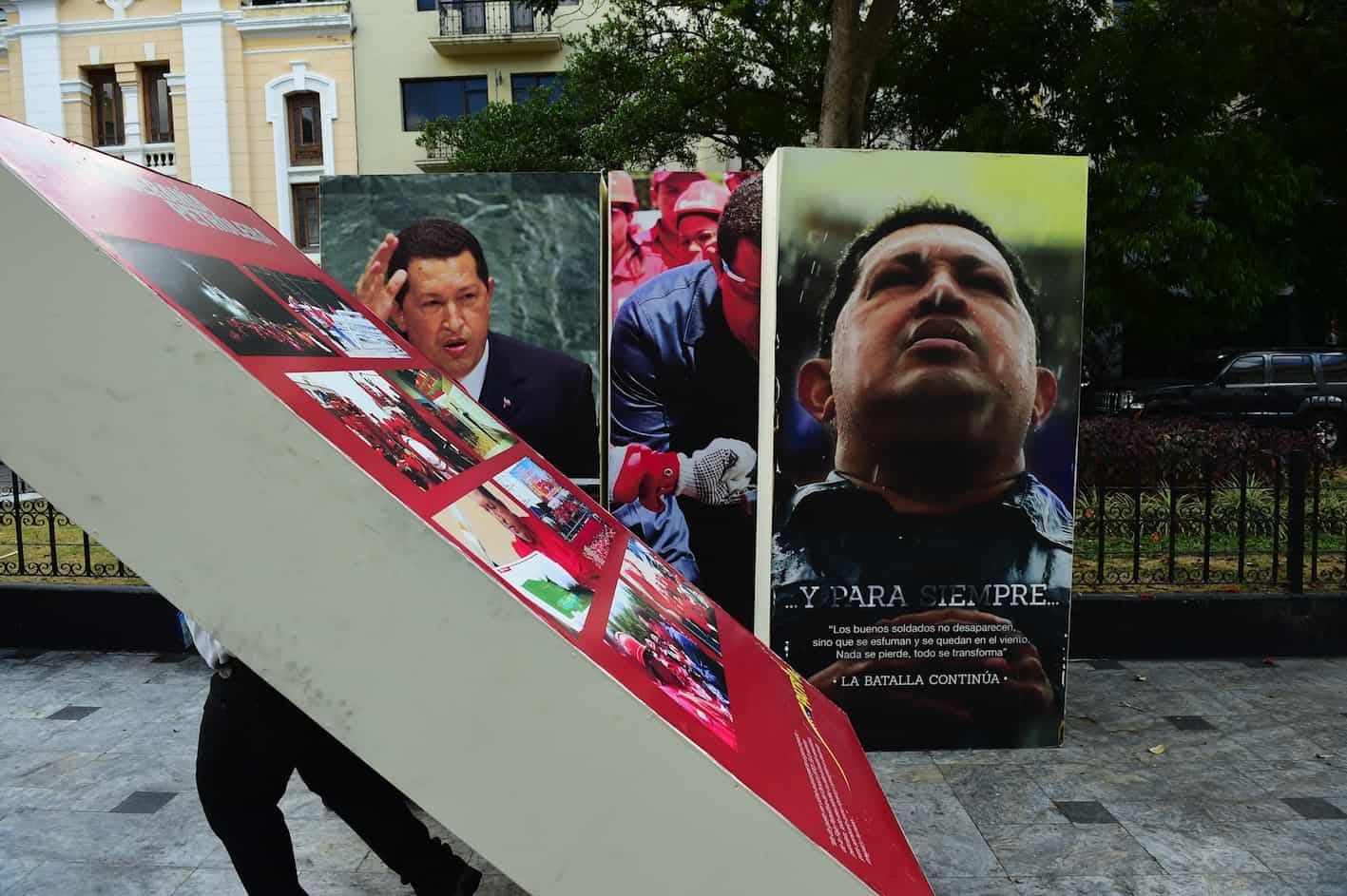 Venezuela National Assembly employees carrying images of Hugo Chávez