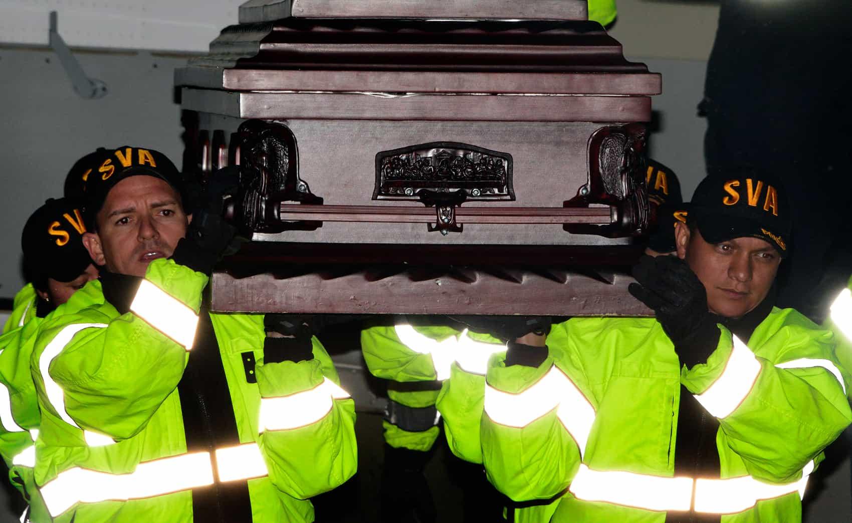 Costa Rican Air Surveillance Service officers escort a body