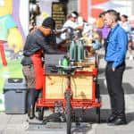 Mariano Marinoni serves coffee to a customer in front of the National Insurance Institute (INS) building.