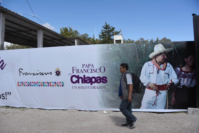 A man passes a banner welcoming Pope Francis near where he will officiate an open-air mass in San Cristobal de las Casas, Chiapas State, Mexico