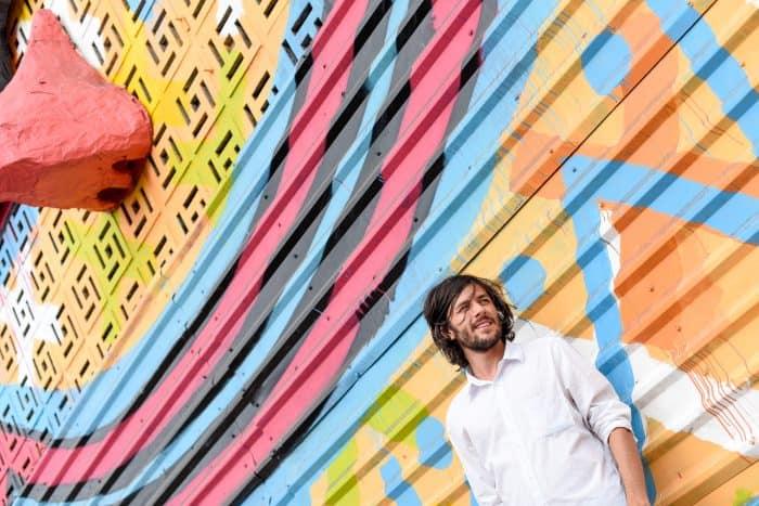 Gussa posing next to his artwork.
