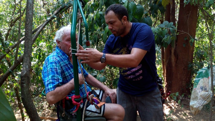 Carlos Jiménez adjusts a safety rope as Jim Smith prepares to ride the EcoTram.