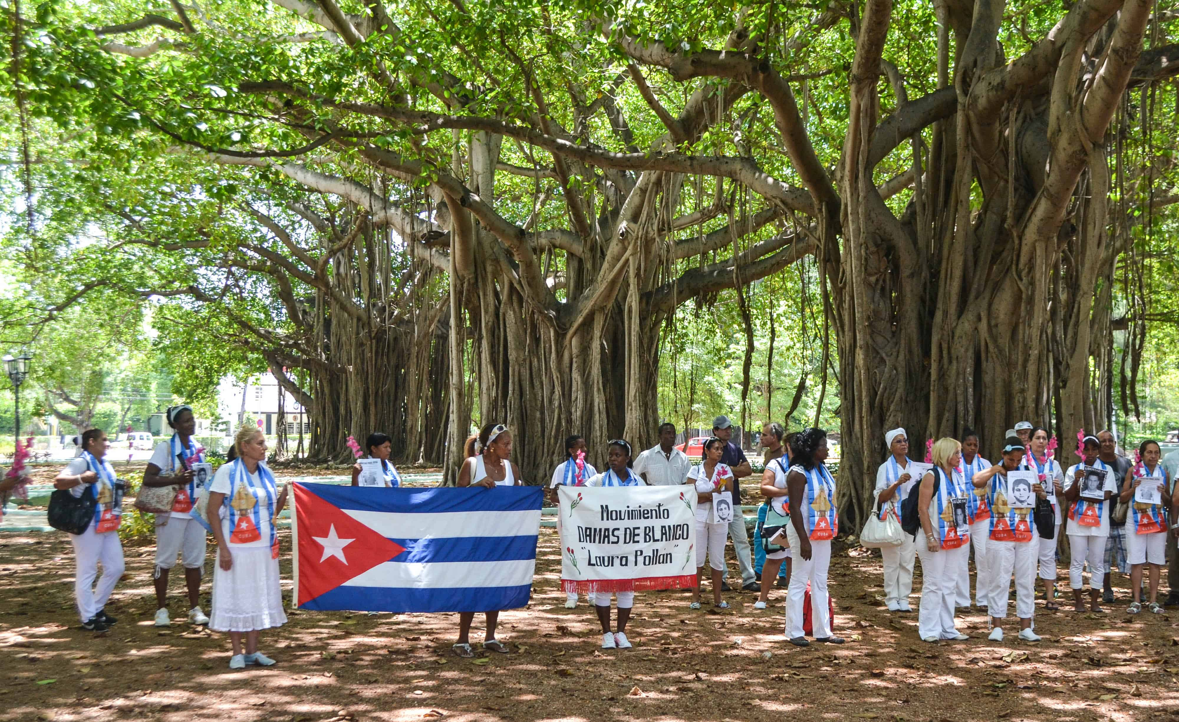 Cuban dissidents and members of the Ladies in White human rights group hold a Cuban national flag and pictures of imprisoned dissidents.