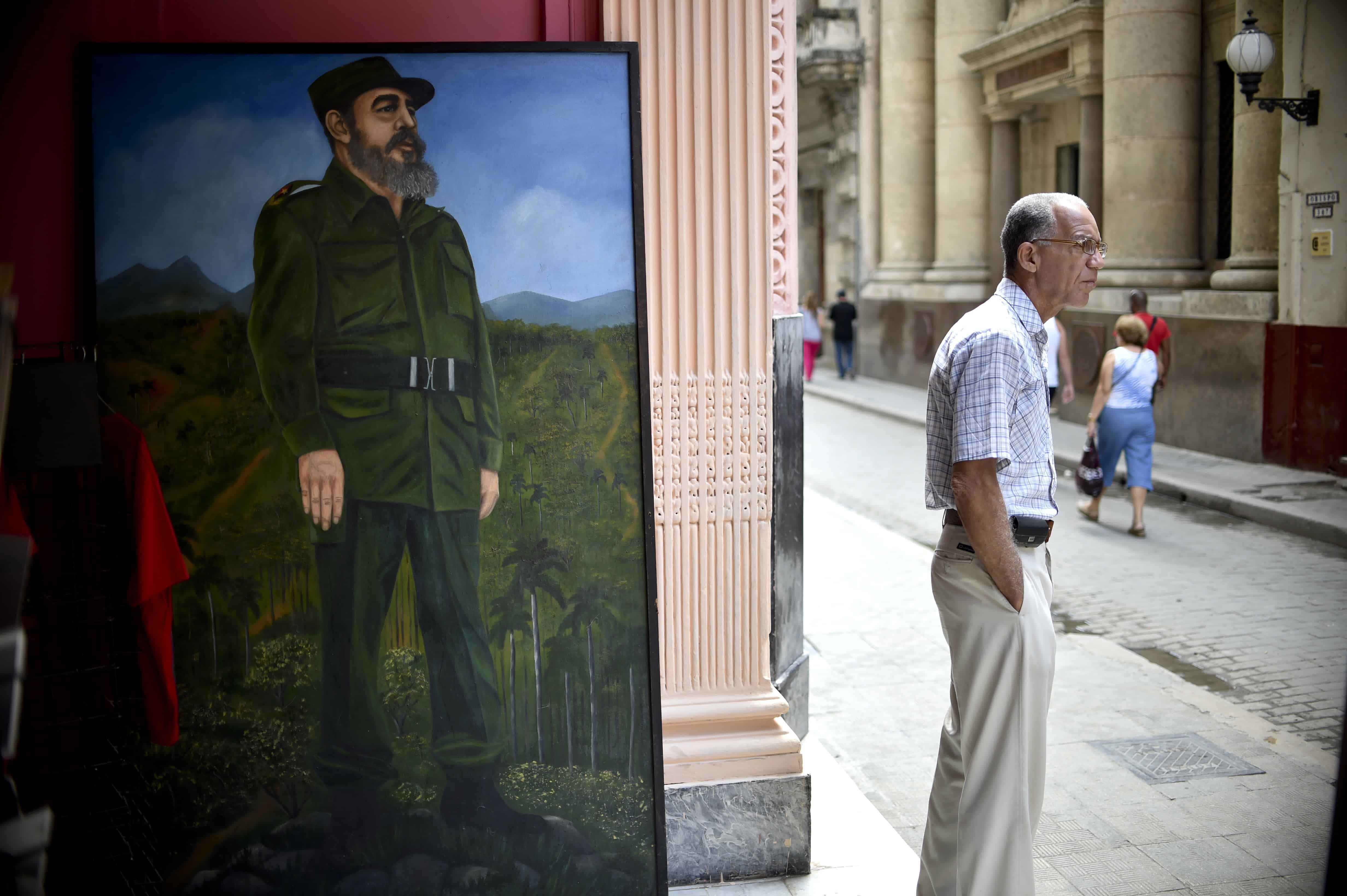 A man stands next to a painting of former Cuban President Fidel Castro