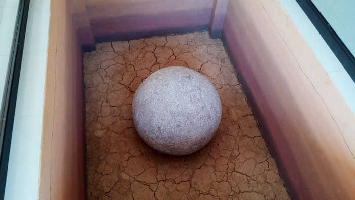 Stone sphere on display inside the museum.