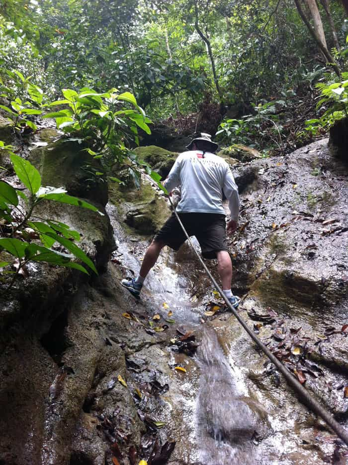 Murphy Allen climbs a waterfall in Matapalo with the aid of a rope.