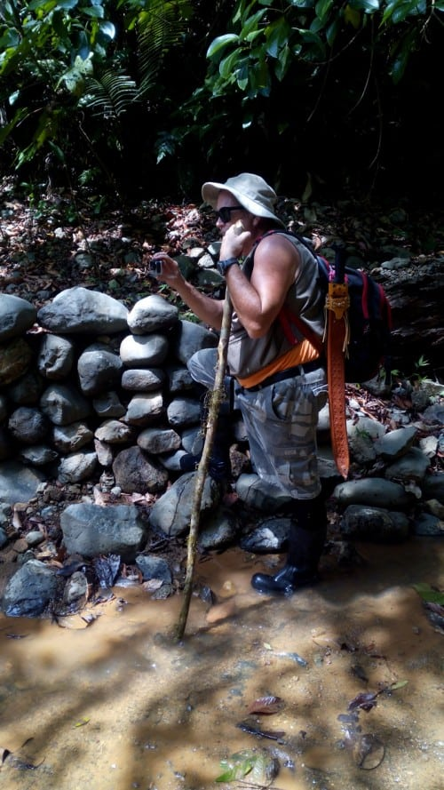 Paul in gold miners' creek, with machete, walking stick and GoPro.
