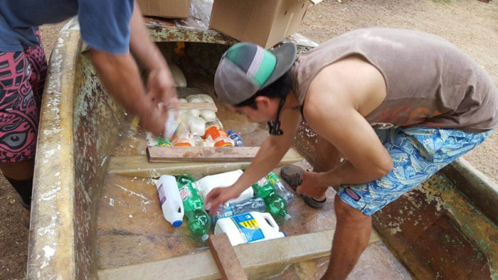 Alberto Robleto Jr. places empty plastic bottles in the bottom of the boat.