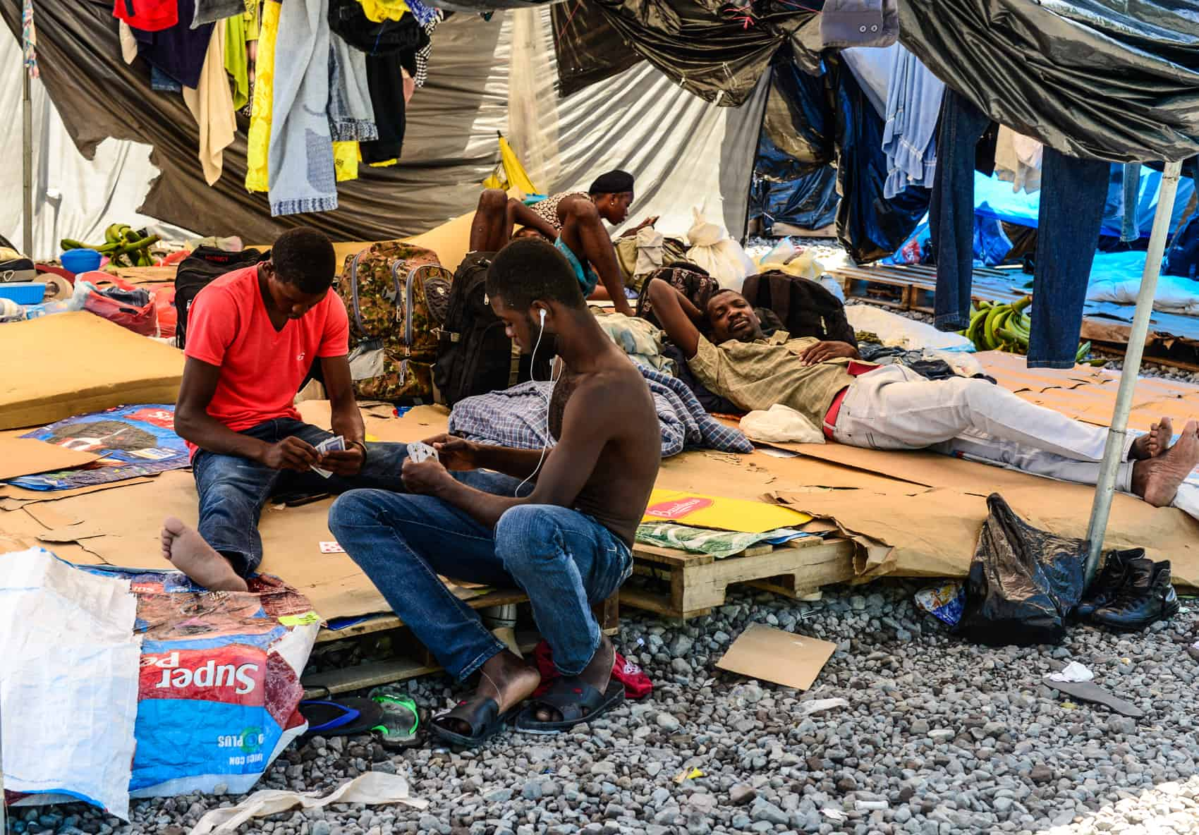 African migrants play cards in a Red Cross tent.