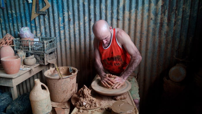 A potter at Cerámica Artística Salitral mashes clay onto a spinning wheel in preparation for making the base for a flowerpot.