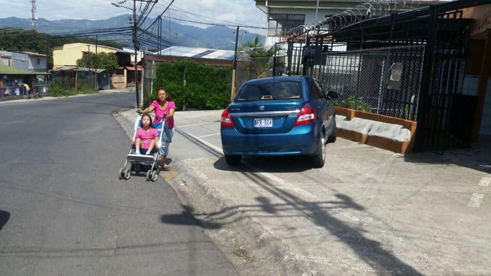 woman with stroller walking in street to get around car parked on sidewalk