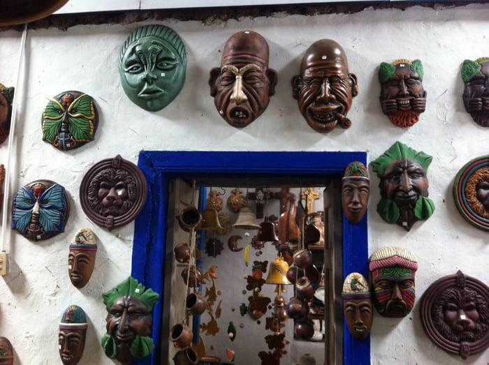 Some masks around a blue door.