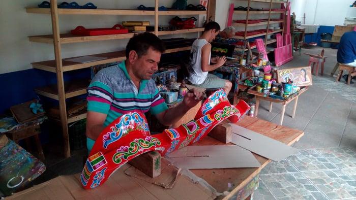 An artist named Edgar paints an oxcart yoke.
