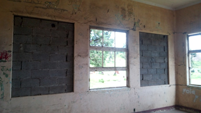 Windows filled with cinder blocks, windows filled with nothing.