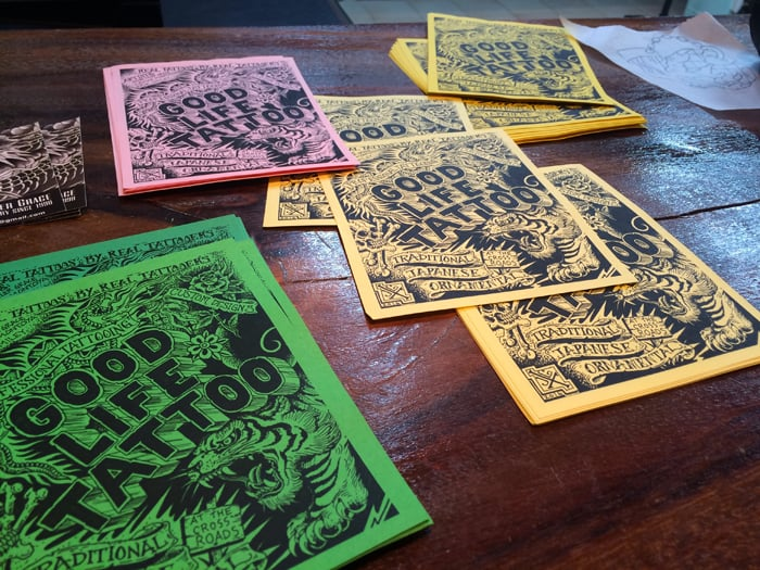 Flyers on the front desk at Good Life Tattoo.