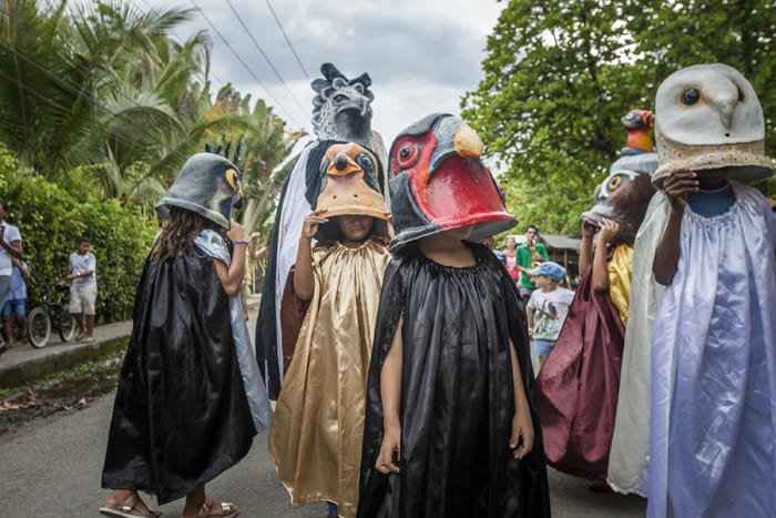 Children dress up as birds in costumes designed by naturalist artist Luis Entique to highlight their importance to this coast.