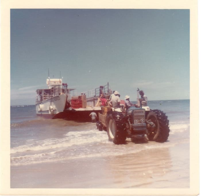 A tractor helps unload a barge on the beach in a 1970s photo.