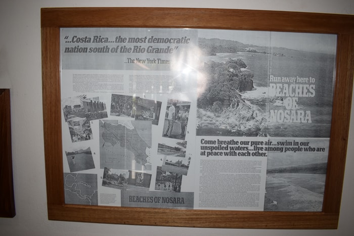"A 1972 ad advertising the ""BEACHES OF NOSARA,"" displayed on the wall at RE/MAX First Choice Realty."