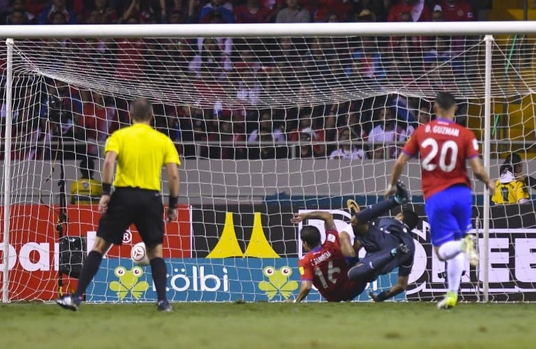 Costa Rica's Cristian Gamboa (16) makes an own goal as Costa Rica's goalkeeper Keylor Navas falls trying to avoid it, during the 2018 World Cup qualifier football match against Mexico in San Jose, on September 5, 2017. / AFP PHOTO / Ezequiel BECERRA