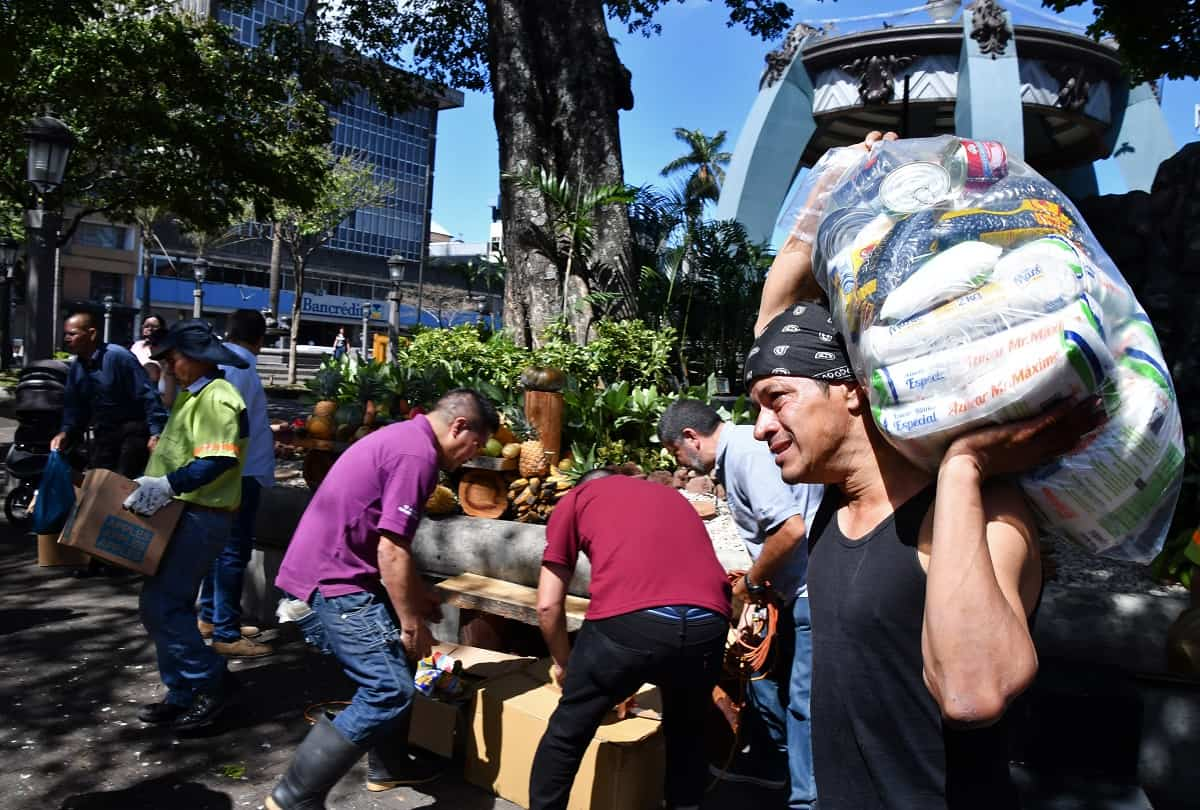 People arrange agricultural products donated for people in need as part of a Holy Week event at San José, Costa Rica's Central Park on March 28, 2018.