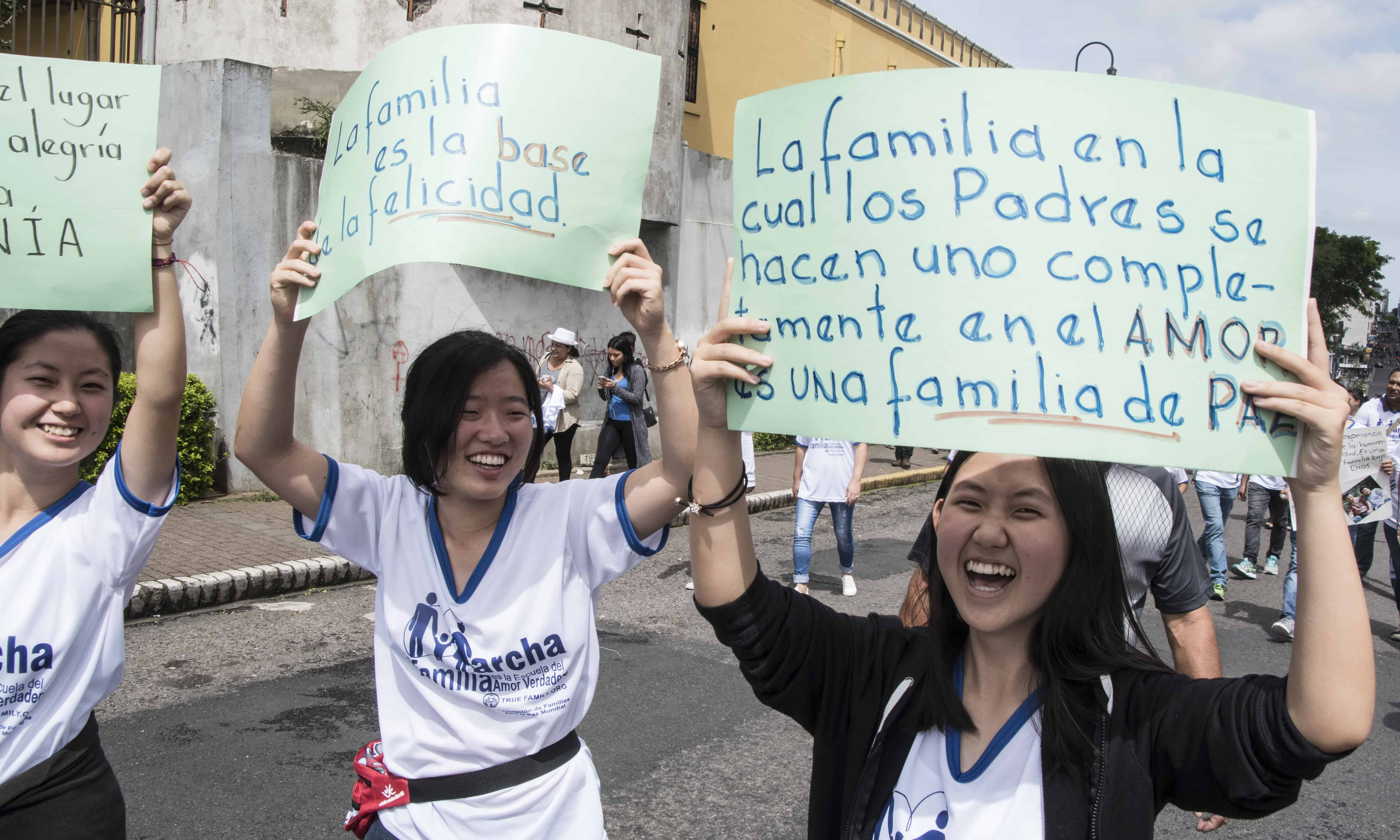 Women hold signs in favor of the traditional family during a march in San José, on July 15, 2018.